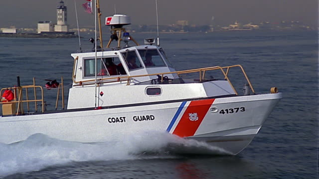 medium shot tracking shot coast guard boat in water off coast of california - coast guard stock videos and b-roll footage