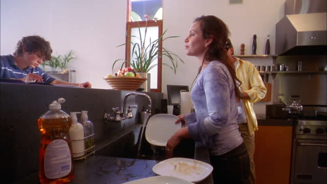 medium shot tracking shot couple rinsing dishes in kitchen sink and putting them in dishwasher / son writing on counter - spülmaschine stock-videos und b-roll-filmmaterial