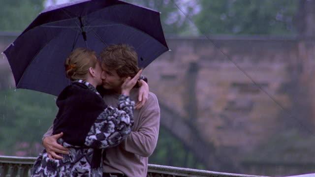 medium shot tracking shot couple walking under umbrella in rain, kissing with charles bridge and vltava river in background / prague - charles bridge stock videos & royalty-free footage