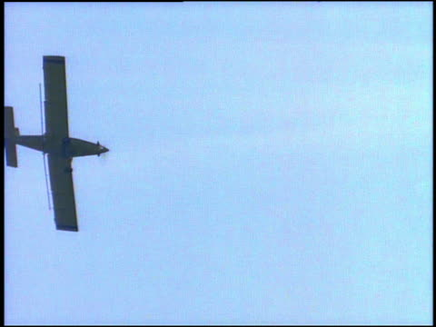 medium shot tracking shot crop duster plane flying low over field spraying insecticide / mississippi - low stock videos and b-roll footage
