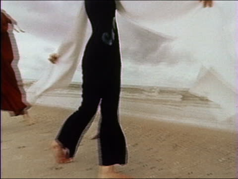 1976 medium shot tracking shot fashion models walking and posing on beach in weird capes + veils / audio - 1976 stock videos and b-roll footage