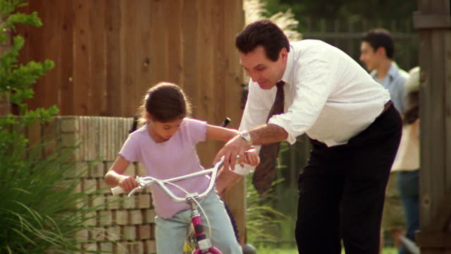 medium shot tracking shot father stopping to help daughter ride bicycle in driveway - chanting stock videos & royalty-free footage