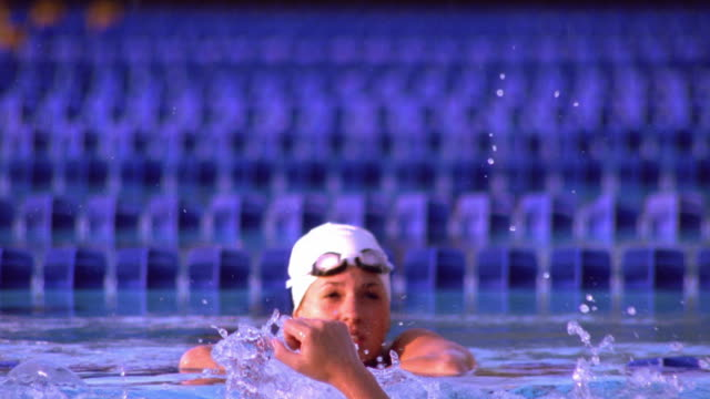 medium shot tracking shot female swimmer celebrating victory in pool / california - success stock videos & royalty-free footage