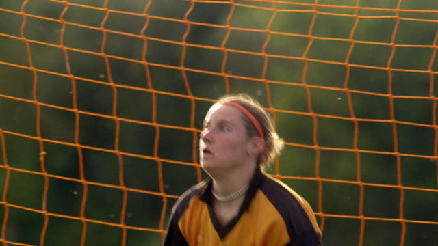 medium shot tracking shot female teenage goalie diving and catching soccer ball / vermont - goalkeeper stock videos & royalty-free footage