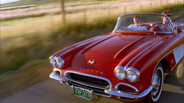 Medium shot tracking shot front view man and young boy driving in 1960s Corvette convertible on rural road
