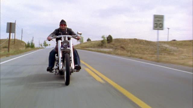 vídeos y material grabado en eventos de stock de medium shot tracking shot front view man riding motorcycle on two lane highway - pasear en coche sin destino