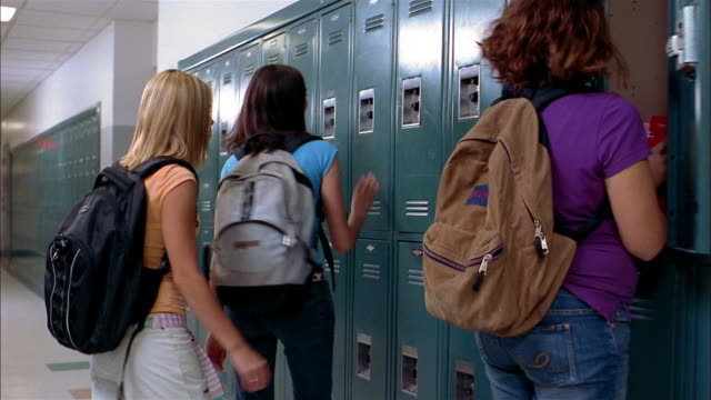 Medium shot tracking shot girl at locker waving to two girls / girls opening lockers / three girls talking