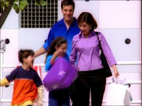 Medium shot tracking shot Hispanic family walking with shopping bags and talking outdoors