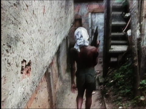 stockvideo's en b-roll-footage met 1991 medium shot tracking shot homeless brazilian boy walking through slum with semiautomatic rifle / brazil - agressie