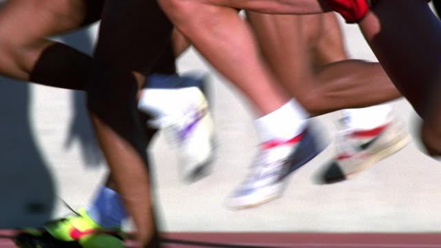 Medium shot tracking shot legs of male runners during race