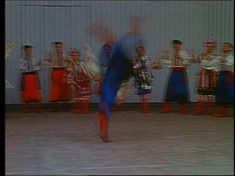 1967 medium shot tracking shot male russian folk dancer doing cartwheels rapidly in a circle with troupe in background / russia - former soviet union stock videos & royalty-free footage