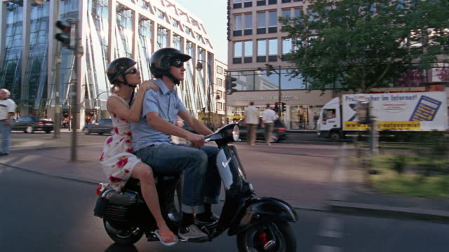 medium shot tracking shot man and woman riding on vespa down street / berlin, germany - motorino video stock e b–roll