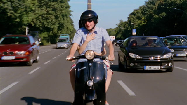 medium shot tracking shot man and woman riding vespa down street / berlin, germany - moped stock videos and b-roll footage