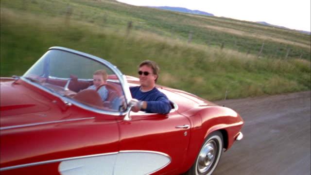 vídeos y material grabado en eventos de stock de medium shot tracking shot man and young boy driving in 1960s corvette convertible on rural road - pasear en coche sin destino