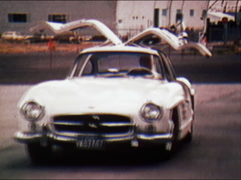 1970 medium shot tracking shot man driving white 1956 gullwing mercedes car with doors that open out and up - mercedes benz stock videos & royalty-free footage