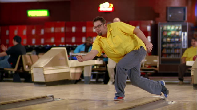 vídeos de stock, filmes e b-roll de medium shot tracking shot man in yellow jersey bowling and cheering / man in blue jersey bowling in league game - cancha de jogo de boliche