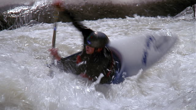 medium shot tracking shot man paddling kayak in rapids / flipping over - 失敗点の映像素材/bロール