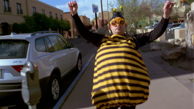 medium shot tracking shot man wearing bee costume dancing on sidewalk - humor stock-videos und b-roll-filmmaterial