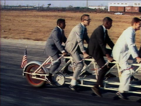 1964 medium shot tracking shot men riding on 11-person tandem bicycle