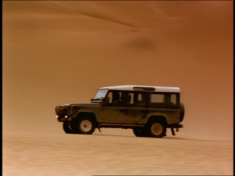 Medium shot tracking shot military humvee and truck driving in desert