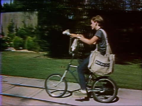 1973 medium shot tracking shot newspaper boy on bike throwing papers at suburban homes - first job stock videos & royalty-free footage