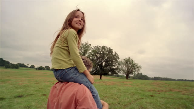 medium shot tracking shot rear view of father putting daughter on shoulders and walking in field / girl looking around - sollevare video stock e b–roll