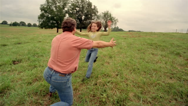 medium shot tracking shot rear view of man kneeling in field / girl running into his arms and smiling at cam - georgia country stock videos and b-roll footage