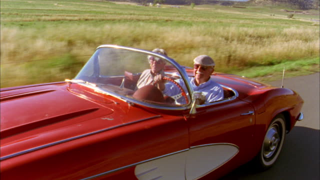 Medium shot tracking shot senior couple driving in 1960s Corvette convertible passing CAM