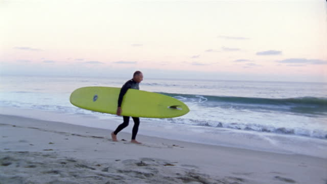 stockvideo's en b-roll-footage met medium shot tracking shot senior man carrying surfboard walking along beach with surf in background - surfbord