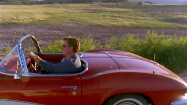 vídeos y material grabado en eventos de stock de medium shot tracking shot side view man and young boy driving in 1960s corvette convertible on rural road - pasear en coche sin destino