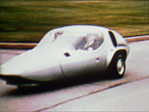 1970 medium shot tracking shot side view of man driving silver fuel-efficient car along road - small stock videos & royalty-free footage