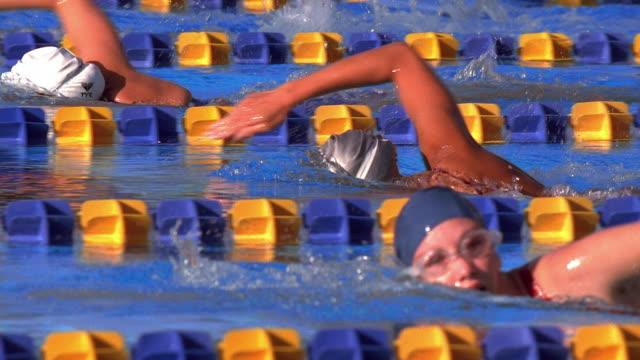 vídeos de stock, filmes e b-roll de medium shot tracking shot slow motion female swimmers racing in pool / california - touca de natação