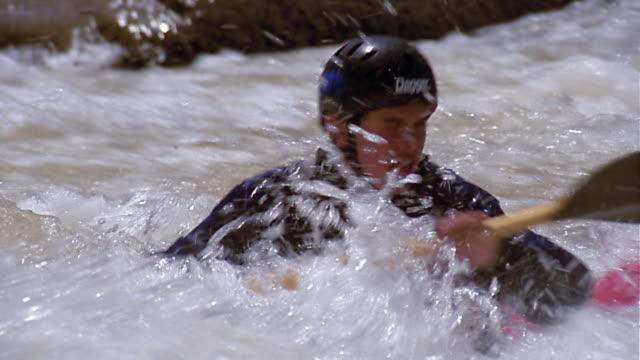 vidéos et rushes de medium shot tracking shot teenage boy paddling kayak / flipping over - kayak sport