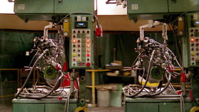 medium shot tracking shot time lapse automobile engines going down assembly line with people working on them / cleveland, ohio - cleveland stock videos and b-roll footage