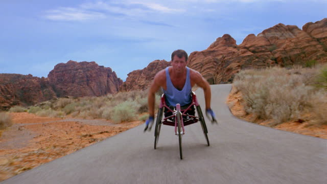 Medium shot tracking shot wheelchair racer turning wheels, then coasting on road in Red Rock Canyon
