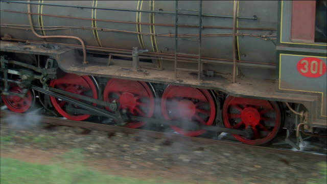 medium shot tracking shot wheels of antique steam train turning along train tracks - dampf stock-videos und b-roll-filmmaterial