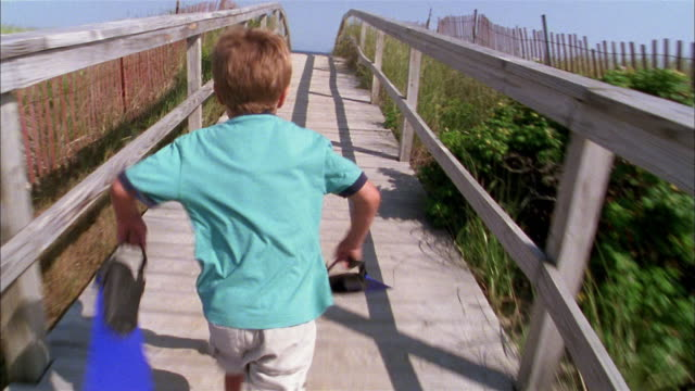 medium shot tracking shot young boy running across footbridge and carrying flippers to beach - shorts stock videos & royalty-free footage