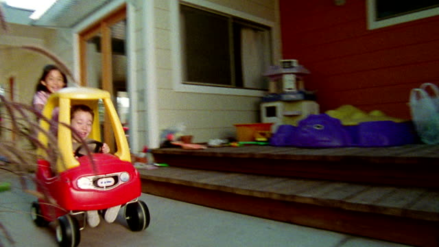medium shot tracking shot young boy sitting in toy car with girl pushing behind him / california - schieben stock-videos und b-roll-filmmaterial