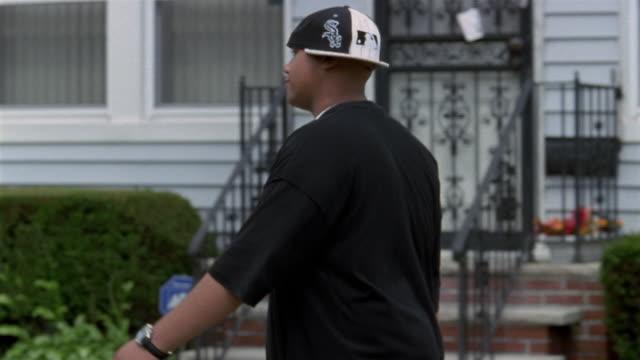 Medium shot tracking shot young man walking down street