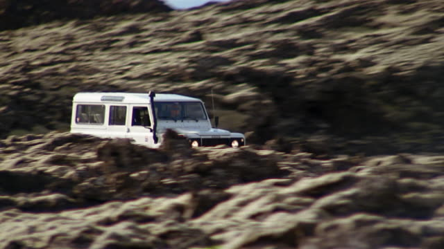 medium shot tracking shot zoom out land rover riding through lava field near the blue lagoon (blaa loninu) / iceland - extreme terrain stock videos & royalty-free footage