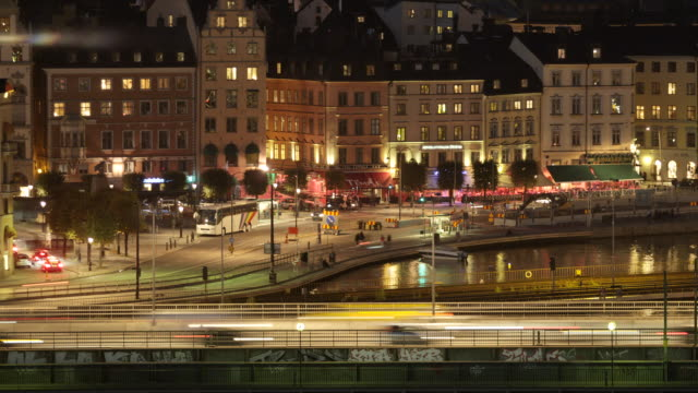 medium shot, traffic moving over the bridge at night, trains passes by, people and cars on street, lights reflect in water, skyline of gamla stan - railroad car stock videos and b-roll footage