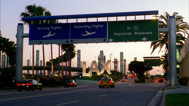 vídeos de stock, filmes e b-roll de medium shot traffic moving past lax airport sign - placa