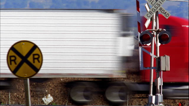 Medium shot traffic passing at railroad crossing with farmland and barn in background / Gustine, California