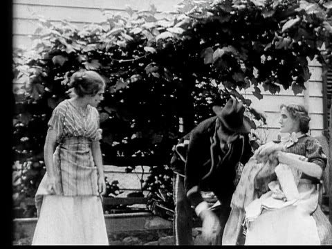 stockvideo's en b-roll-footage met 1910 b/w medium shot tricky salesman pitching to woman and her maid  - 1900 1909