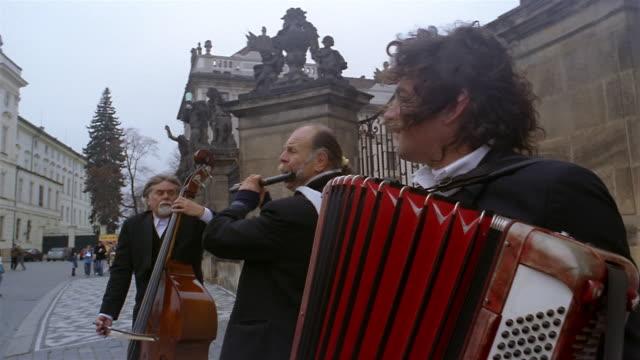 vídeos y material grabado en eventos de stock de medium shot trio of muscians performing on the street / prague - república checa