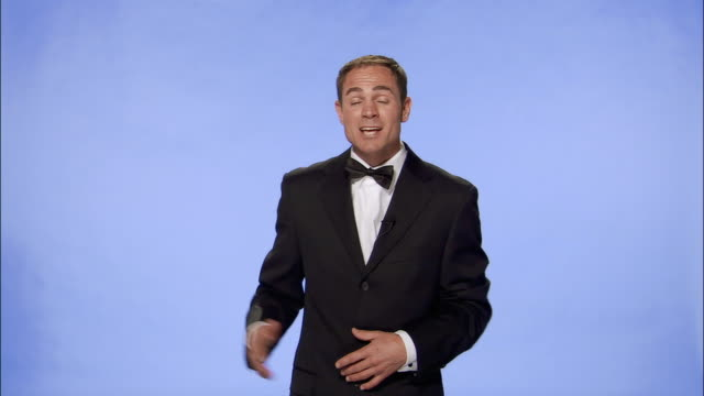 Medium shot TV presenter in tuxedo talking to camera and gesturing against blue screen/ London