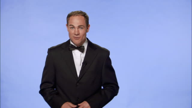 medium shot tv presenter in tuxedo talking to camera and gesturing against blue screen/ london - dinner jacket stock videos & royalty-free footage