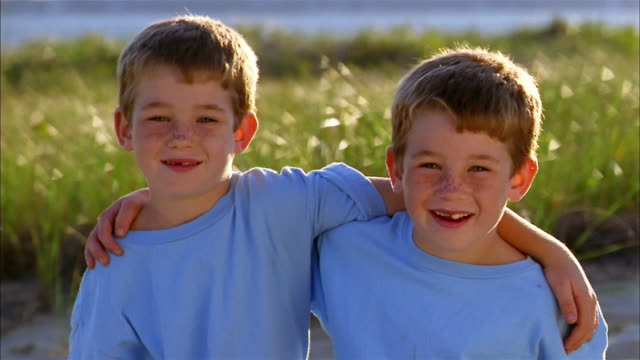 medium shot twin freckle-faced boys arm-in-arm smiling at cam - fratello video stock e b–roll