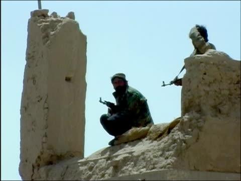 vidéos et rushes de medium shot two afghan guards with guns standing atop damaged building on watch / ghazni afghanistan - armée nationale afghane