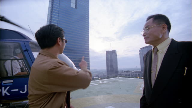 Medium shot two Asian businessmen talking and pointing on building rooftop